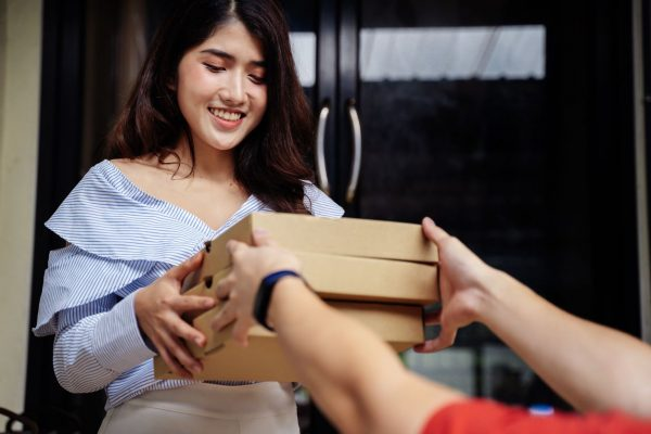 Portrait of happy smiling Asian woman in casual clothing receiving a pizza packaging box from delivery man. Fast food order from customer at home. Food delivery service concept. (Portrait of happy smiling Asian woman in casual clothing receiving a piz