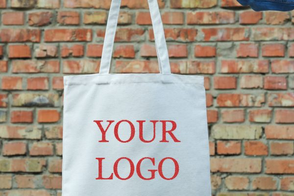Female hand holding tote bag against brick wall, empty space